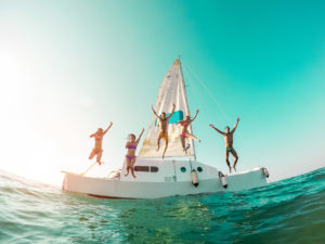 Happy crazy friends diving from sailing boat into the sea - Young people jumping inside ocean in summer vacation - Main focus on center guys - Travel and fun concept - Fisheye lens distortion
