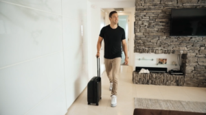 Lewis Howes walking with NOMATIC roller luggage